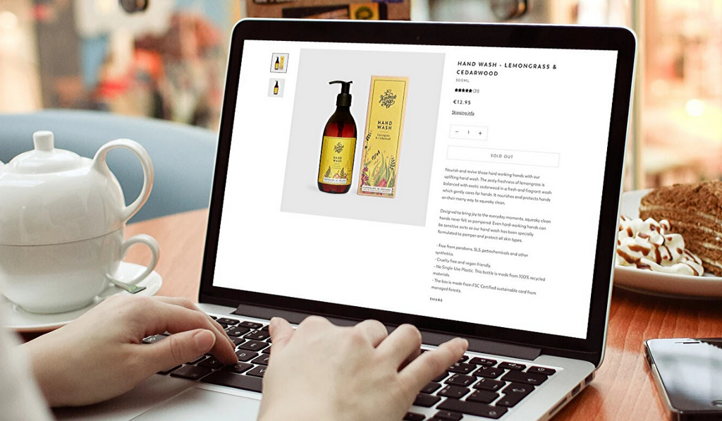 The Handmade Soap Company product page showing on a laptop with a pot of tea and slice of cake in background.