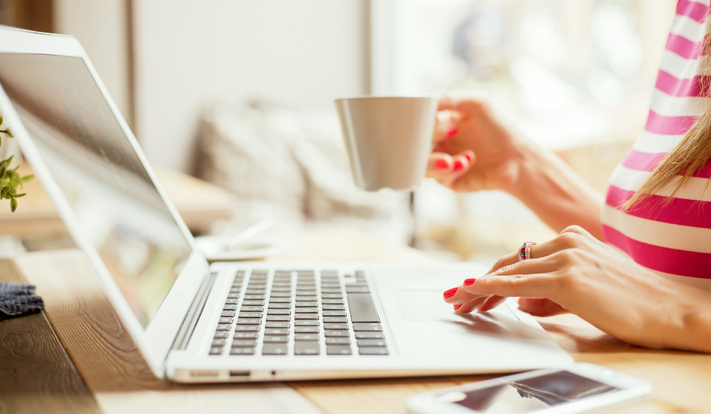 Female hand holding cup of coffee tea scrolling on white laptop