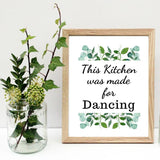 KQ111810 Quote in black text that reads this kitchen was made for Dancing on a white background green watercolor foliage is on top and on the bottom of the quote