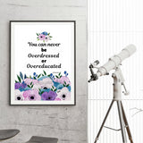 quote reads you can never be over dressed or overeducated in black text on white background and pink purple and blue flowers across bottom framed in black frame hanging from wall with a standing telescope next to it to show its size which is 18x 24 inches