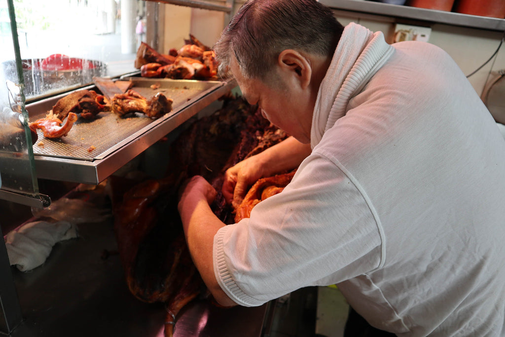 while the joss paper is burning, the roasted pigs are sent upstairs to be cut into smaller portions