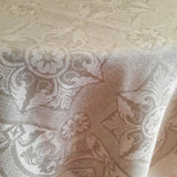 Natural light grey linen tablecloth with a classic ornament on an oval table