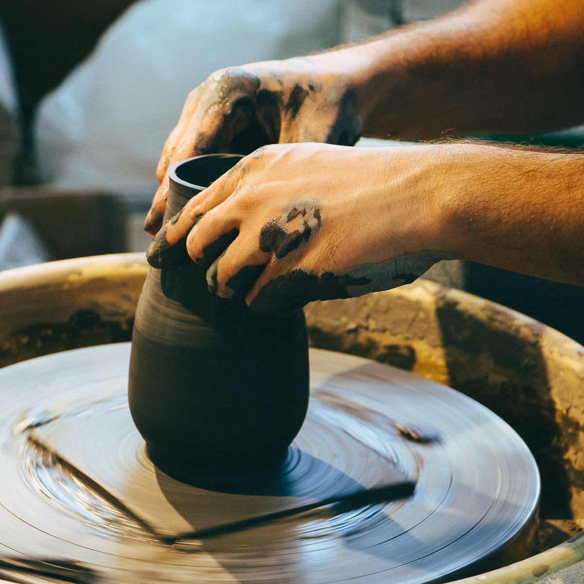 Christian Roy Hand Throwing Ceramics in His Workshop