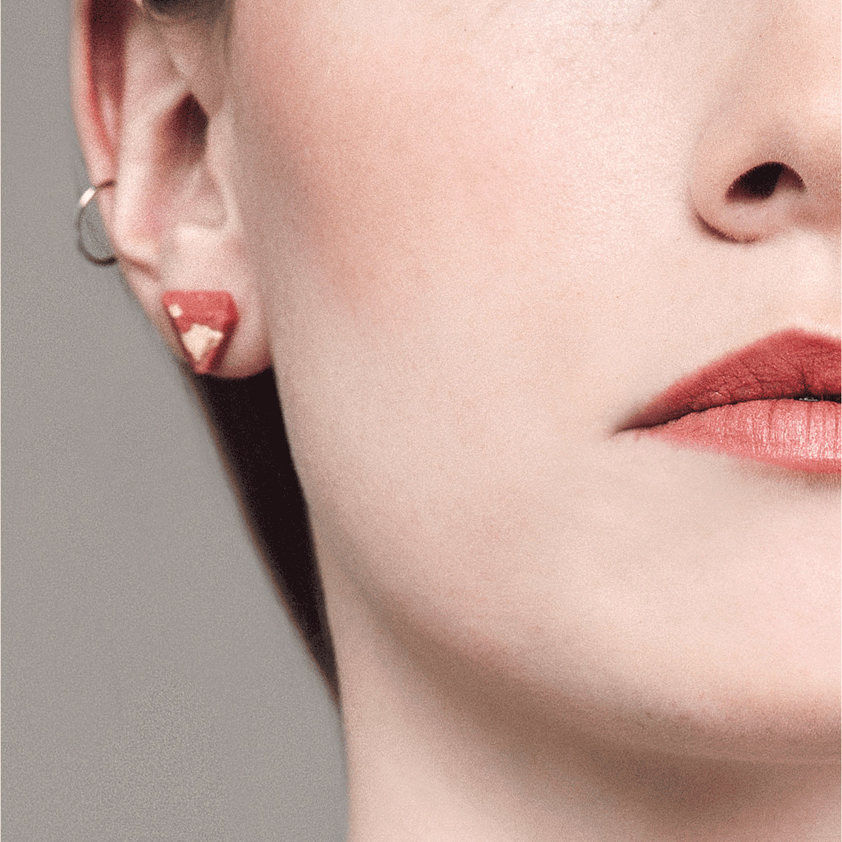 Woman Wearing a Coral Diamant Stud Earrings - Handmade in Eco-friendly Resin & Gold Leaf - Sold by Chic & Basta