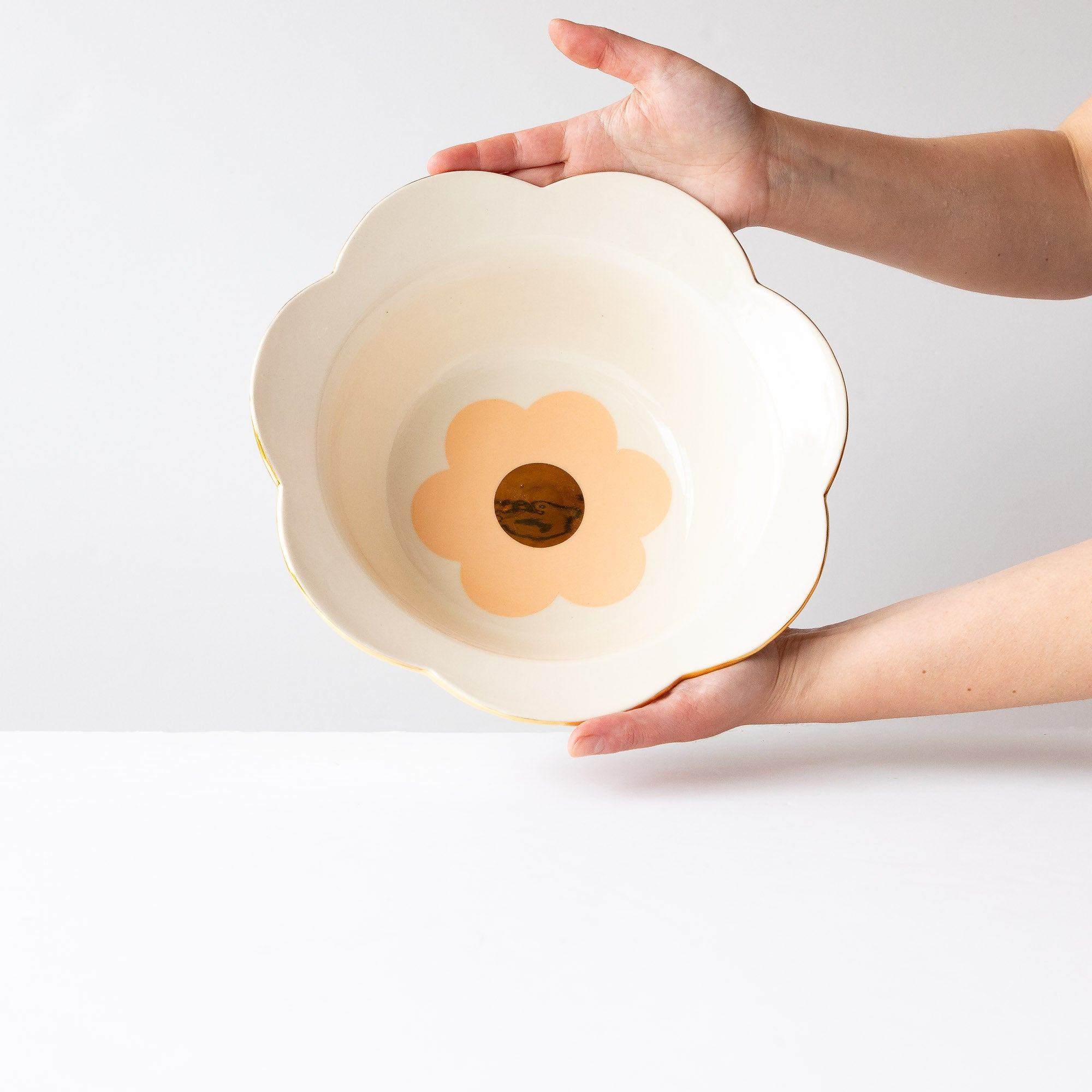 Hands Holding a Handmade Porcelain Tangerine Daisy Salad Bowl with Gold - Sold by Chic & Basta
