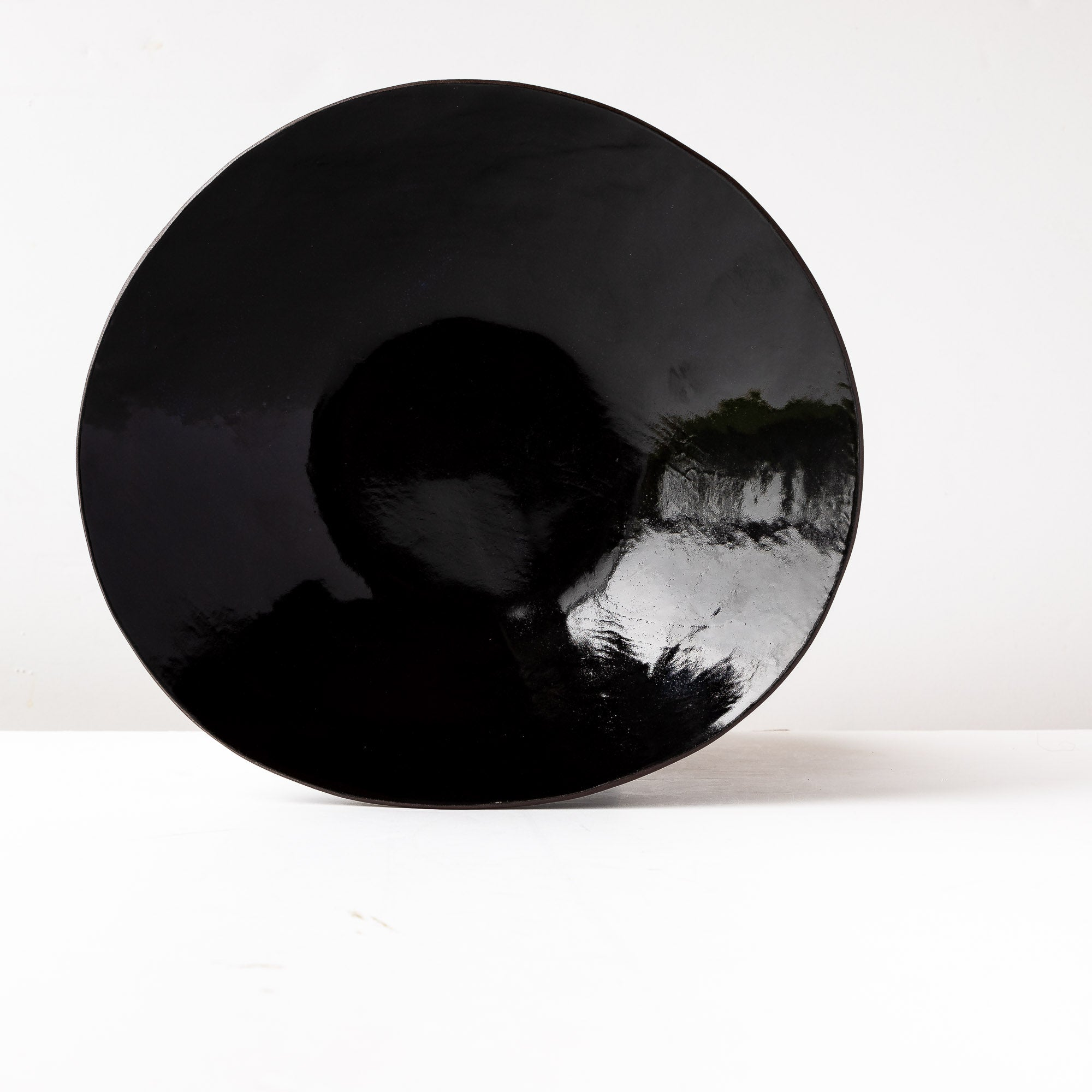 Hand Holding a Handcrafted Large Fruit Bowl in Black Lacquered Stoneware - Sold by Chic & Basta