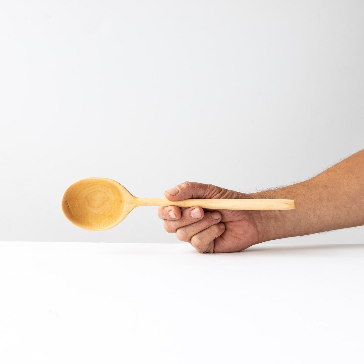 Hand Holdding a Hand-carved Basswood Ladle - Sold by Chic & Basta
