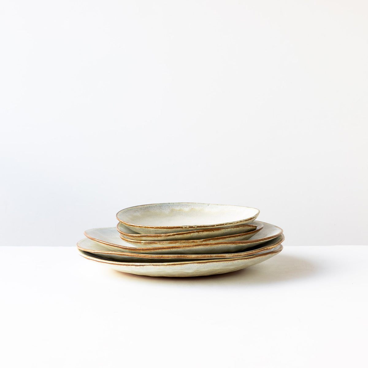 A Pile of Medium & Large Handbuilt Plates in Red Stoneware & Cream Glaze - Sold by Chic & Basta