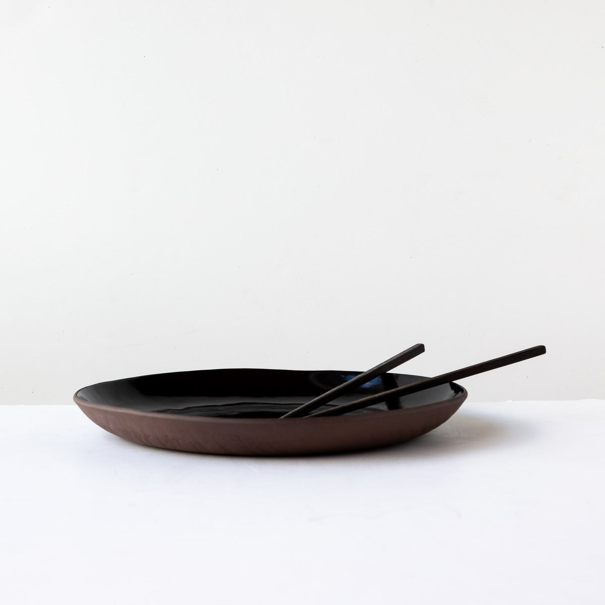 Side View with Chopsticks - Handmade Large Plate in Black Lacquered Stoneware - Sold by Chic & Basta
