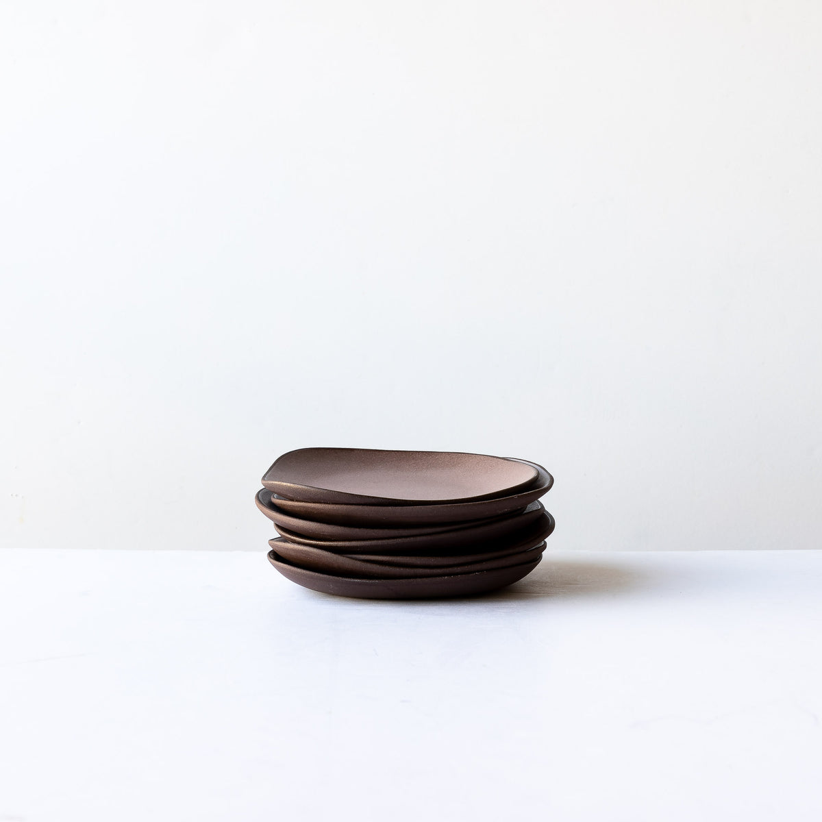 A Pile of Handcrafted Organic Shaped Small Stoneware Plates - Sold by Chic & Basta