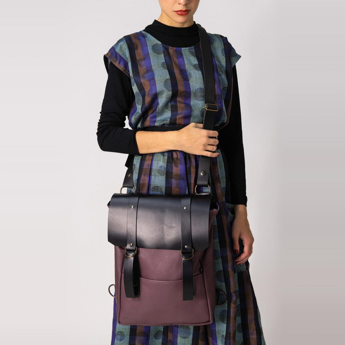 Model Wearing a Purple & Black Handcrafted Leather Backpack / Crossbody Bag - Sold by Chic & Basta