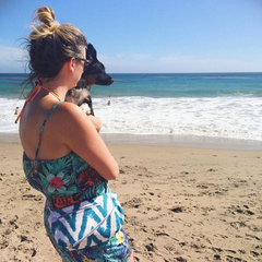 Woman holding a dog and wearing a blue Beach Wave fanny pack at the beach