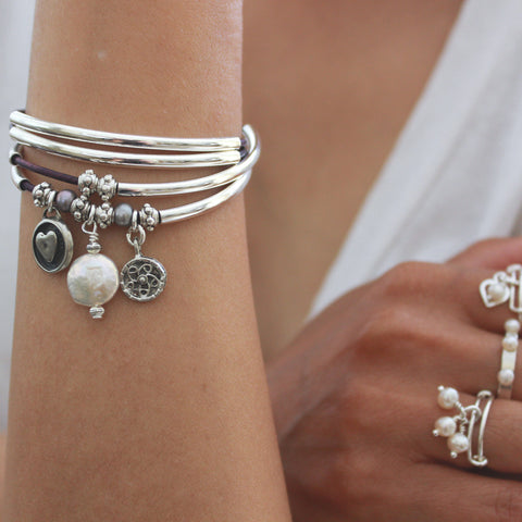 Mini Charmer with Pearl charm trio leather wrap bracelet, shown with assorted sterling silver rings, sold separately