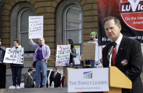"""Chief Justice Moore of Alabama giving a speech on his """"traditional marriage"""" stance, with protestors in the background. Via the AP."""