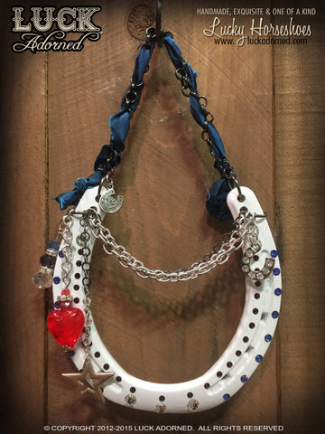 AMERICAN STYLE is a glossy white lucky horseshoe, hung by a gunmetal chain with a shimmery, blue ribbon through it.