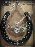 LOVE ROCKS Luck Adorned Lucky Horseshoe is a glossy black horseshoe with a big, chunky, silver heart in the center, accented with white diamond Swarovski crystals, all hanging from funky silver chain.