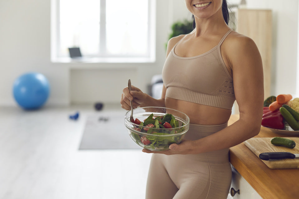 Healthy woman eating a salad after a workout.