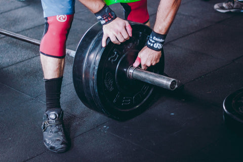 crossfitter loading weights onto a barbell