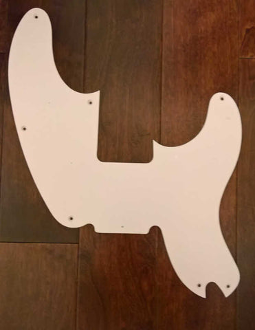 The Fender 1-ply 7-hole 51 Precision Bass Pickguard in white on a brown wood floor.