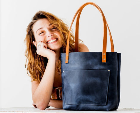 Best Sellers happy smiling girl with handmade Portland leather goods deep water blue navy tote bag