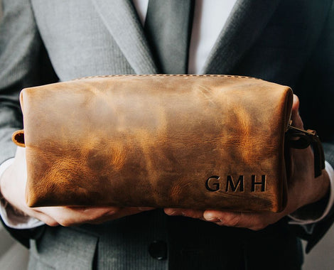 Groomsmen Gifts leather handmade dopp kits in distressed brown canyon with bride and groom wedding setting made in Portland Oregon