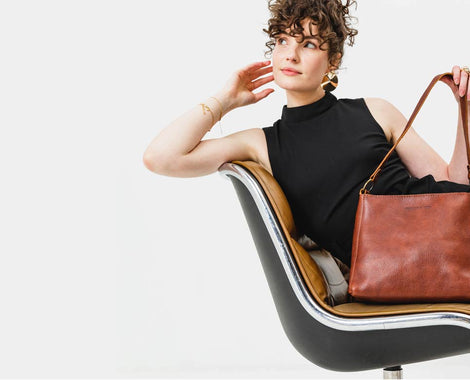Leather purses and handbags by Portland Leather Goods, image shows mini totes in wine red, cognac brown, honey brown, green, blue and black.