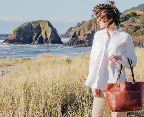Happy Woman with book and honey brown full grain leather tote hand bag hand made by Portland Leather Goods