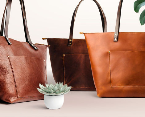 Collection of full grain leather zipper totes with bridle leather handles next to monstera and succulent, handmade by Portland Leather Goods