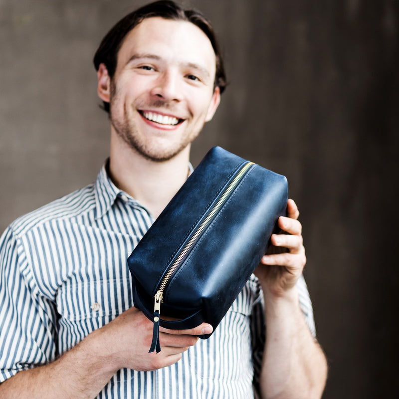 Happy man with deep water navy blue leather zipper dopp kit