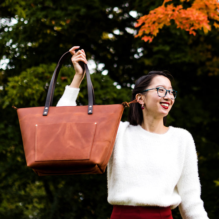 Leather tote bag in front of autumn fall leaves