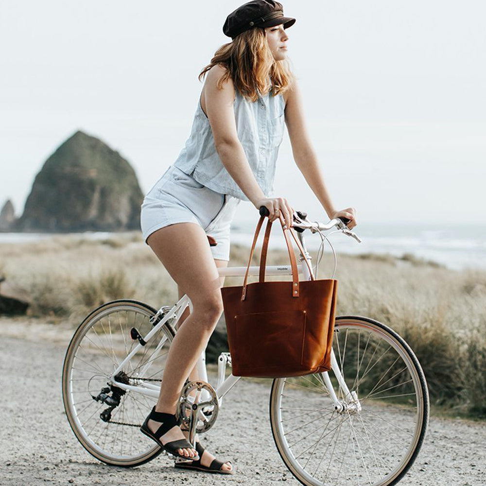 Girl riding bike at beach with Leather Classic Tote
