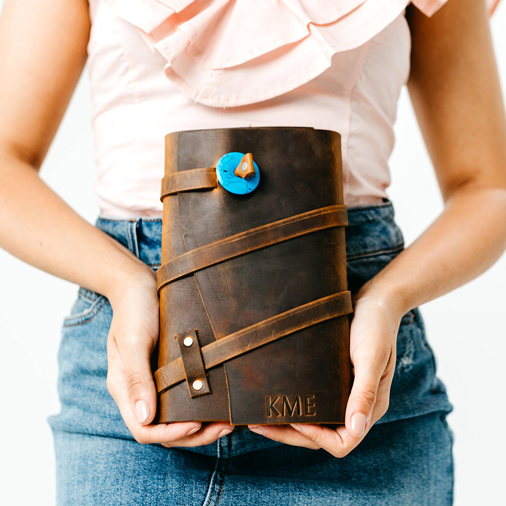 happy girl holding personalized leather journal in hickory