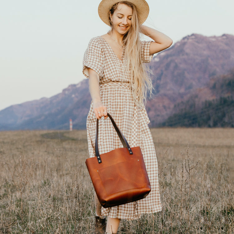 Happy Girl with book and brown leather tote purse bag