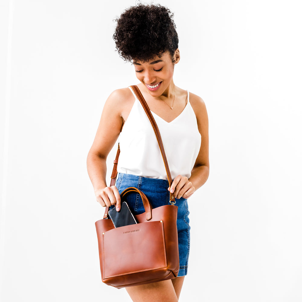 Girl Reading next to Grizzly Leather crossbody tall tote handmade Portland Oregon