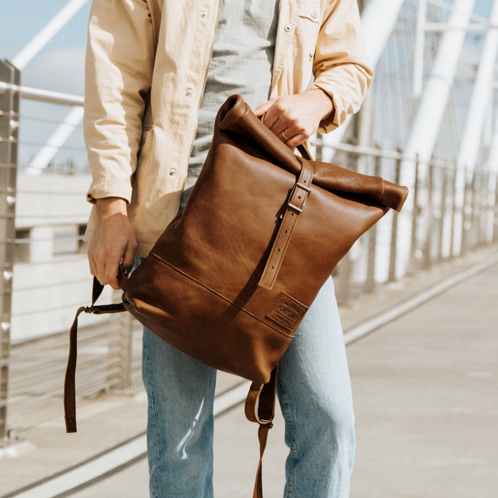 Happy bearded man holding leather roll top backpacks