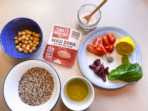 An overhead shot of a packet of Wild Zora Tomato Basil Soup on a kitchen counter surrounded by various ingredients in bowls.