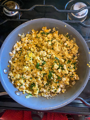 An overhead shot of a skillet on a stove filled with scrambled tofu, seasoned with turmeric for a yellow color and a packet of Wild Zora Roasted Pumpkin Soup.