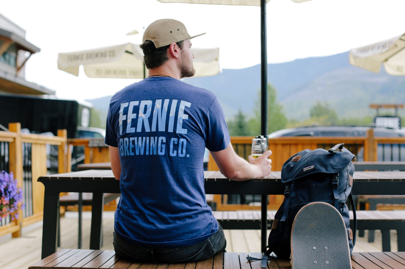 Man in blue shirt sits on a patio drinking a beer with a skateboard and bag to his right.