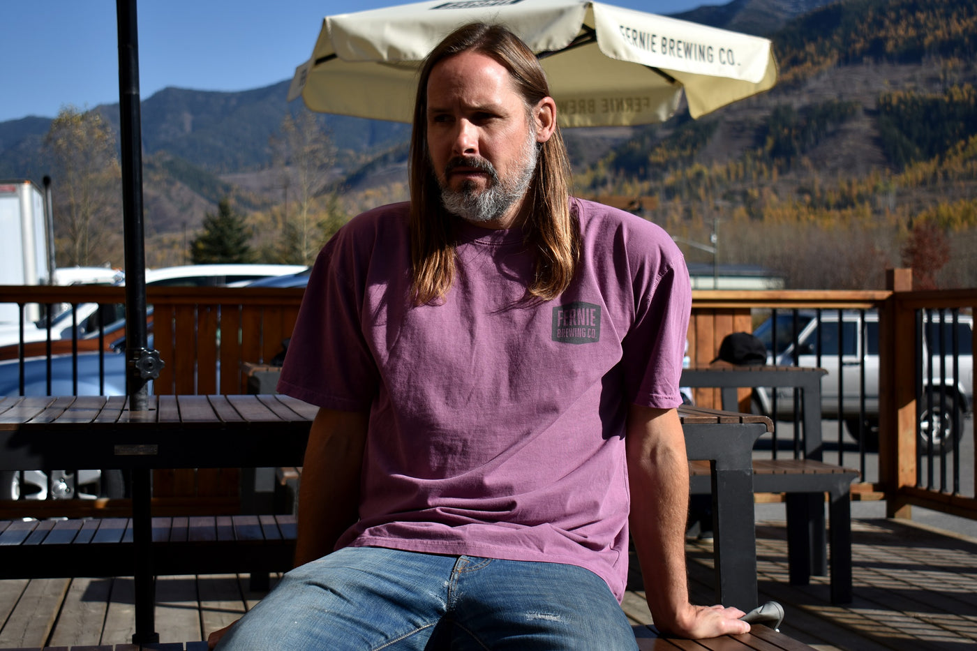 Man sat on patio wearing grey t-shirt and black hat reaching into his bag.