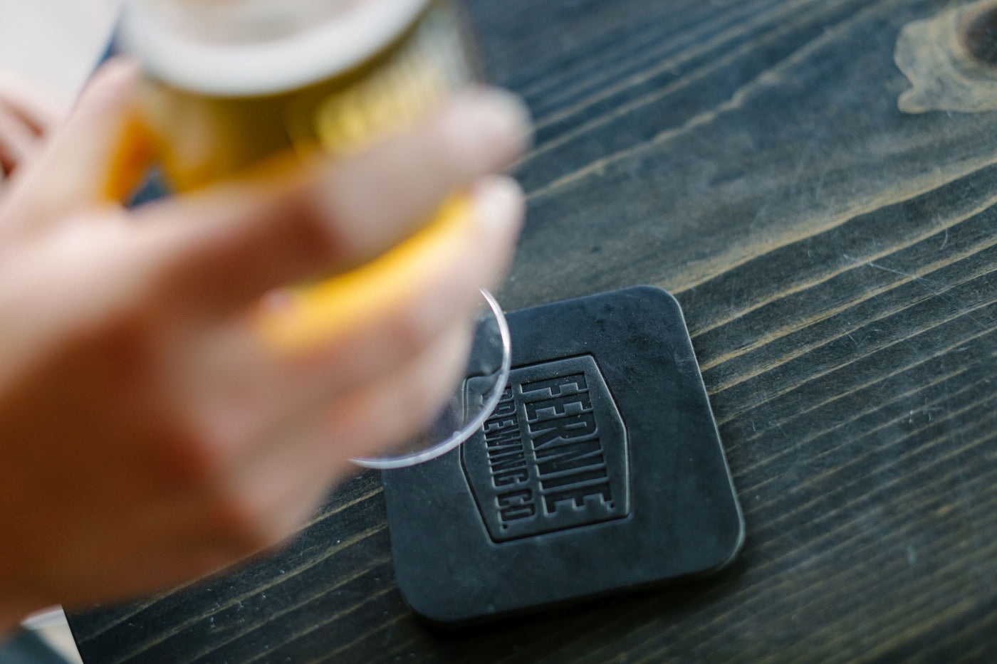 Glass of beer being lifted off of leather coaster.