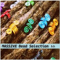 An assortment of different coloured spiral dreadlock hair beads displayed fitted onto dreadlocks