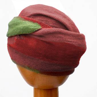 A Fair Trade Tie Dye Stretch Cotton Dreadlock Headwrap/Dreadwrap in Green, Rust and Brown colours shown on wooden mannequin head