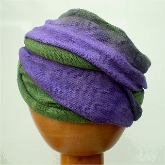 A Fair Trade Tie Dye Stretch Cotton Dreadlock Headwrap/Dreadwrap in Purple and Green colours shown on wooden mannequin head