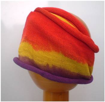 A Fair Trade Tie Dye Stretch Cotton Dreadlock Headwrap/Dreadwrap in Purple, Orange and Yellow colours shown on wooden mannequin head