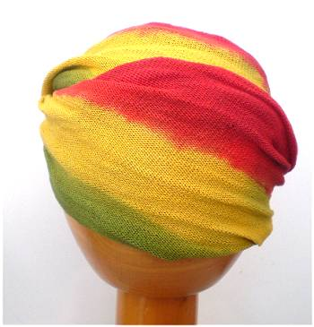 A Fair Trade Tie Dye Stretch Cotton Dreadlock Headwrap/Dreadwrap in Red, Green and Yellow colours shown on wooden mannequin head