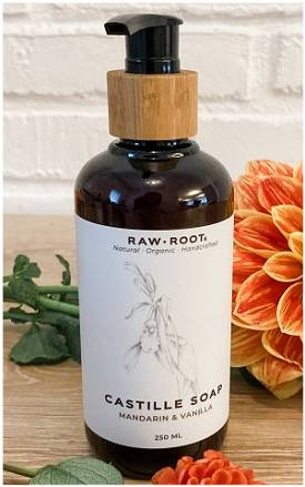 A 250 millilitre bottle of Mandarin and Vanilla scented RAW ROOTS Natural Organic Castille Shampoo/Soap displayed on a wooden table top with flowers in front and behind