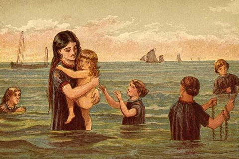 Mother holds baby in her arms in the ocean water along with other children