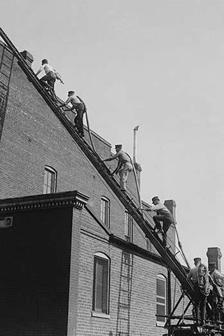 A team of Firefighters with Hoses on Their backs climbs a ladder