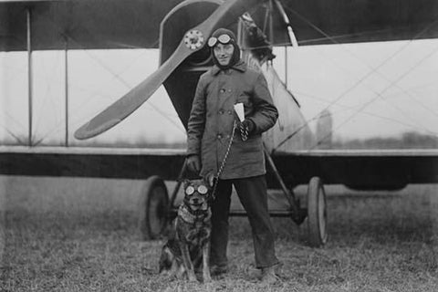 Aviator and His dog wear goggles in front of his Biplane