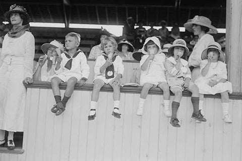 Children sit on wall in front of stands at the ballpark and eat ice cream cones.